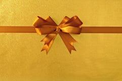 金礼物弓丝带,发光的金属箔纸背景,平直水平 免版税库存照片