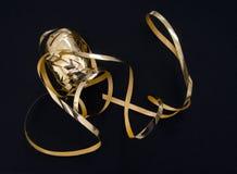 金缎带包装磁带,在黑织品背景的丝带 库存图片