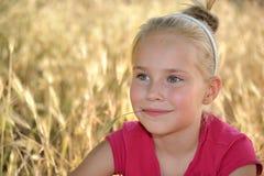 金草背景的微笑的小女孩  免版税库存照片