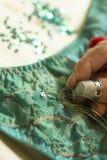 金螺纹通过在绿色服装的一块衣服饰物之小金属片 免版税图库摄影
