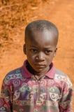 金迪亚,几内亚- 2013年12月28日:未认出的非洲男孩画象有红色土路的在背景中 库存图片
