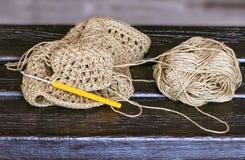 金钩针和未完成的编织的左边由织毛衣者在长木凳 免版税库存照片