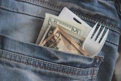 金钱、卡片钥匙和叉子在雇员的蓝色牛仔裤的一个口袋赶紧在午休时间特写镜头的 快餐的概念 免版税库存图片