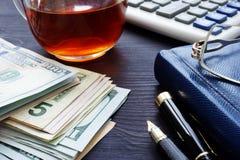 金钱、茶,计算器和笔记本在桌上 应计额 免版税库存照片