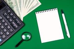 金钱、计算器和笔记本在绿色背景 免版税库存图片