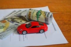 金钱、购买契约和一辆红色汽车在一张木桌上 免版税库存图片