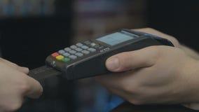 金钱交易的信用卡机器 有信用卡重击的人手通过pos终端和键入别针代码 股票视频