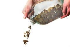 金钱从在白色背景的一个玻璃瓶子倾吐了 免版税库存图片