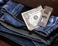金钱和一个手提箱有牛仔裤的 库存图片