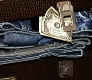 金钱和一个手提箱有牛仔裤的 图库摄影