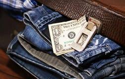 金钱和一个手提箱有牛仔裤的 免版税库存照片