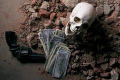 金钱和一把左轮手枪在头骨附近 犯罪概念 库存图片