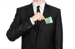 金钱和企业题材:拿着一钞票100欧元的一套黑衣服的一个人被隔绝在白色背景在演播室 库存图片