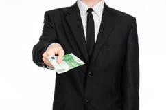 金钱和企业题材:拿着一钞票100欧元的一套黑衣服的一个人被隔绝在白色背景在演播室 库存照片