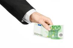 金钱和企业题目:在拿着一钞票100欧元的一套黑衣服的手被隔绝在白色背景在演播室 免版税库存图片