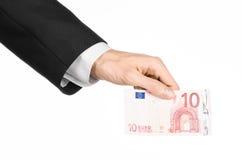 金钱和企业题目:在拿着一钞票10欧元的一套黑衣服的手被隔绝在白色背景在演播室 免版税库存照片