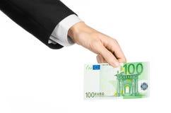 金钱和企业题目:在拿着一钞票100欧元的一套黑衣服的手被隔绝在白色背景在演播室 免版税库存照片