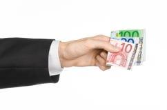 金钱和企业题目:在拿着钞票10,20和100的一套黑衣服的手在白色的欧元在演播室隔绝了背景 免版税库存照片