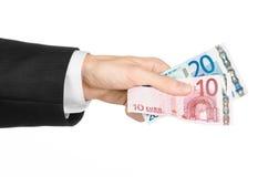 金钱和企业题目:在拿着钞票10和20的一套黑衣服的手在白色的欧元在演播室隔绝了背景 库存照片
