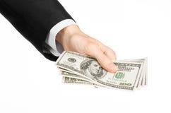 金钱和企业题目:在拿着100美元的钞票在白色的一套黑衣服的手在演播室隔绝了背景 免版税库存图片