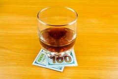 金钱和威士忌酒 免版税库存照片