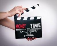 金钱和时间平衡 拿着电影拍板的女性手 免版税库存照片