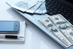 金钱和电子设备 免版税图库摄影