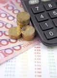 金钱和计算器有图的在书桌上 免版税库存图片