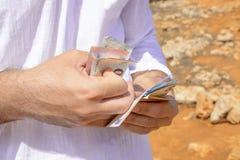 金钱在一个人的手上一个温暖的假日 免版税库存照片