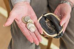 金钱在一个年长妇女` s手和钱包上 免版税库存图片