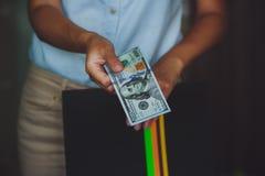 金钱在人的手,给美元的妇女上 免版税库存图片