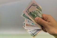 金钱在有金钱的,拿着钞票的手手手上, 免版税库存图片