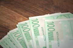金钱在木桌上的一百欧元 库存图片
