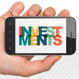 金钱概念:拿着有投资的手智能手机在显示 库存图片