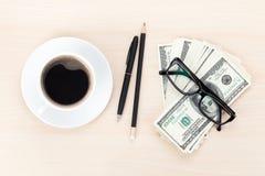 金钱现金、玻璃、笔和咖啡杯 免版税库存图片