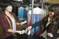 付金钱的顾客到洗衣店所有者 免版税库存照片