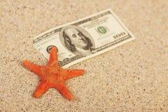 金钱美国人在沙子和红色橙色星的一百元钞票钓鱼 免版税图库摄影