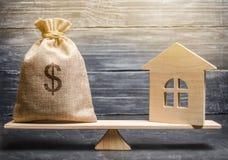 金钱袋子和一个木房子等级的 房地产购买的概念 物产销售  抵押的付款 库存照片