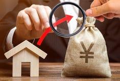 金钱袋子和一个红色箭头在一个人的手上在房子附近 不动产市场成长的概念 涨价 库存照片
