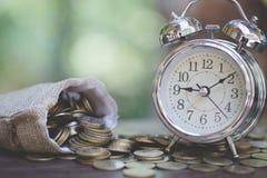 金钱袋子和时钟在木桌上有自然背景,金钱储款,堆积增长的硬币,存金钱为未来 库存照片