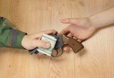 金钱调动以交换一杆枪的在某一情况下 免版税库存照片