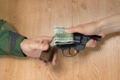 金钱调动以交换一杆枪的在某一情况下 免版税库存图片