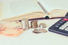 金钱钞票,在堆的硬币,在一本开放书前面的一个计算器 昂贵的教育和低奖学金的概念 库存照片