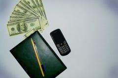 金钱,笔记薄,电话 免版税库存图片