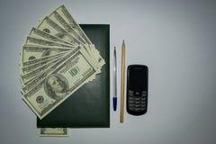 金钱,笔记薄,电话 免版税库存照片