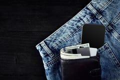 金钱,聪明,转账卡和信用卡在蓝色牛仔裤的口袋在木背景的与拷贝空间 免版税图库摄影
