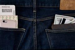 金钱,聪明,转账卡和信用卡在蓝色牛仔裤的口袋 免版税库存图片
