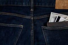 金钱,转账卡和信用卡在蓝色牛仔裤的口袋在木背景的与拷贝空间 免版税库存照片