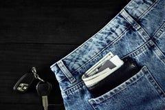 金钱,转账卡和信用卡在蓝色牛仔裤,在木背景的汽车钥匙的口袋与拷贝空间 免版税库存图片