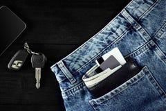 金钱,转账卡和信用卡在蓝色牛仔裤,汽车钥匙的口袋,聪明在与拷贝空间的木背景 库存照片